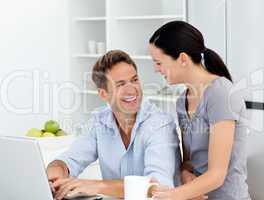 Happy couple working on their laptop in the kitchen