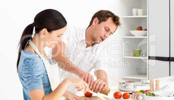 Man putting salt and pepper while his girlfriend stiring the sau