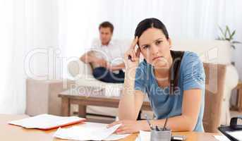 Worried woman doing her account while her boyfriend waiting in t