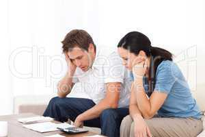 Worried couple looking at their bills on the sofa