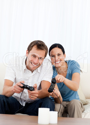 Excited couple playing video games together on the sofa