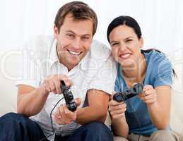 Joyful couple playing video games together on the sofa