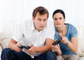 Concentrated couple playing video games together on the sofa