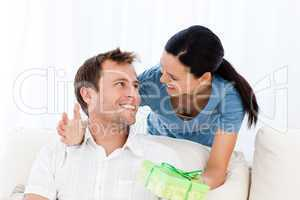 Happy man receiving a present from his girlfriend