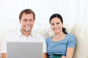 Relaxed couple with laptop and credit card sitting on the sofa