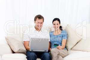 Happy couple buying online with laptop and credit card on the so
