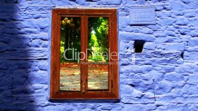Looking through old cottage window at colorful autumn leaves