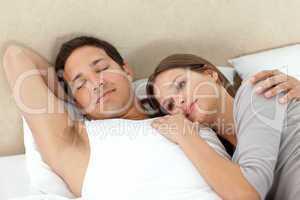 Serene woman lying on her boyrfriend's arms while sleeping