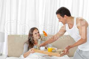 Attentive man serving the breakfast to his girlfriend on the bed