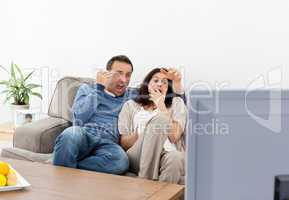 Scared couple watching a horror movie on the television