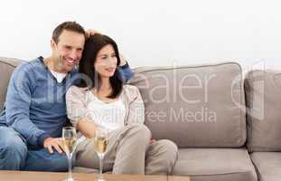 Relaxed couple watching television while drinking champagne