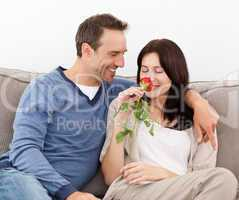 Lovely man looking at his girlfriend smelling a red rose