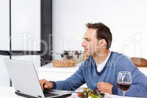 Concentrated man looking at his laptop while eating a salad
