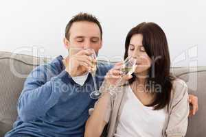 Relaxed couple drinking champagne on the sofa