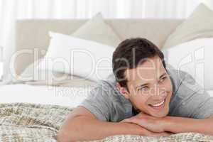 Cheerful man lying in his bedroom