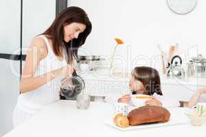 Pretty mom pouring coffee while her children having breakfast