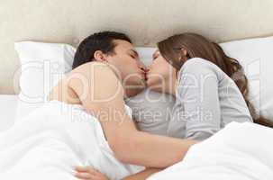 Lovely couple kissing in each other's arms on the bed