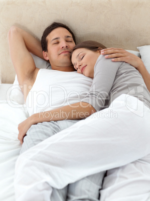 Cute couple sleeping in each other's arms on their bed