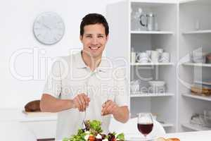 Happy man preparing a salad while drinking red wine