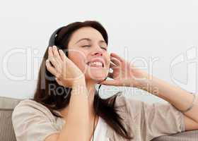 Happy woman enjoying a song on the sofa