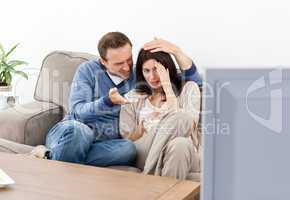 Scared woman watching a horror movie with her boyfriend
