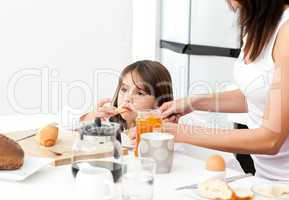 Pretty mother giving toast with jam to her daughter for the brea