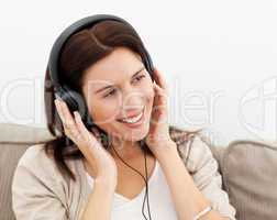 Happy woman with headphones sitting on the sofa