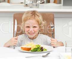 Excited boy holding forks to eat pasta and salad