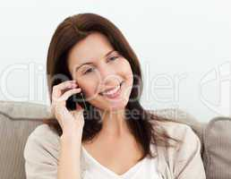 Happy woman on the phone sitting on the sofa
