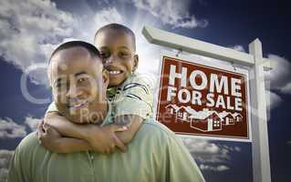 African American Father with Son In Front of Real Estate Sign