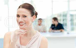 Smiling businesswoman looking at the camera while her coworkers