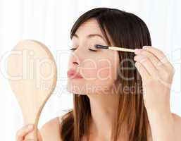 Beautiful woman putting on Make up