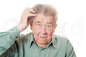 Senior kratzt sich verlegen den Kopf