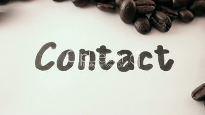 contact.  written on white under coffee