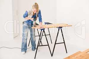 Home improvement - handywoman cutting wooden floor