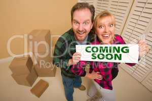 Goofy Couple Holding Coming Soon Sign in Room with Boxes