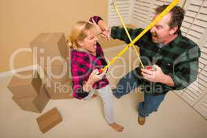 Couple Having Fun Sword Fight with Tape Measures