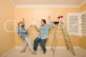 Fun Couple Playing Sword Fight with Paint Rollers