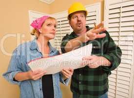 Contractor in Hard Hat Discussing Plans with Woman