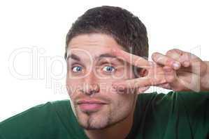 Junger Mann schaut durch zwei Finger