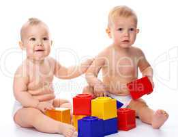 Two children play with building bricks