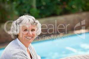 Smiling woman beside the swimming pool