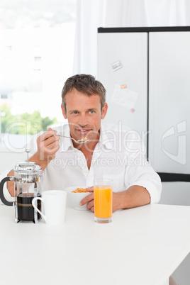 Handsome man having his breakfast in the kitchen