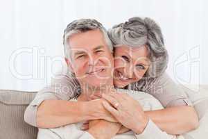 Mature couple looking at the camera at home