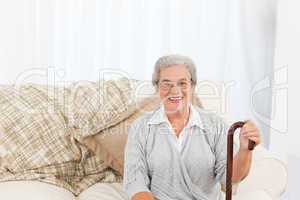 Mature woman sitting on the sofa with her walking stick