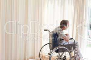 Man in his wheelchair looking out the window