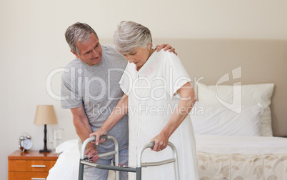 Man helping his wife to walk