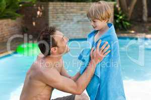 Father with his son beside the swimming pool