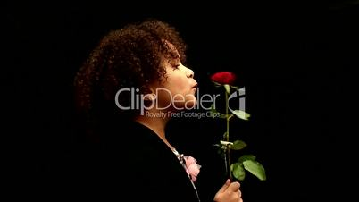 Young black girl/child with curly hair holding a red rose against black background 3