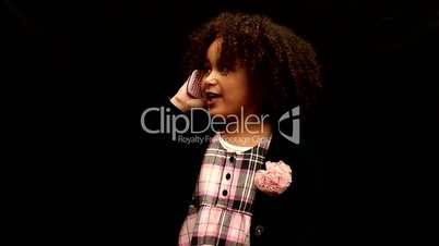Young black girl/child with curly hair talking on mobile phone against black background 3